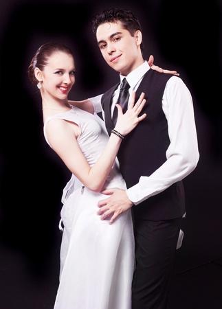 beauty contest: a couple dancing against black studio background