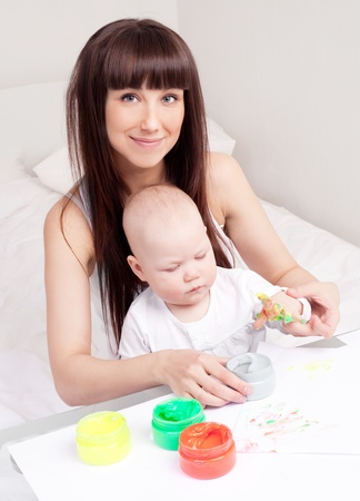 single parent: happy mother and daughter painting at home