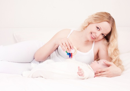 happy young mother and her four months old daughter in bed at home Stock Photo - 13331181