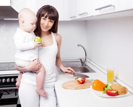 beautiful  young woman holding her baby and cutting vegetables for the salad in the kitchen Stock Photo - 13331198
