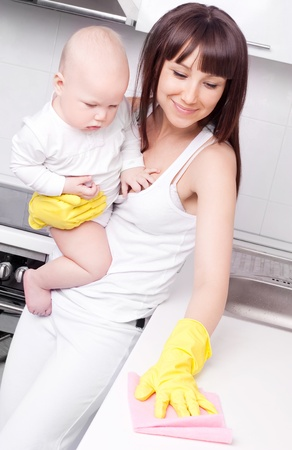 clean kitchen: beautiful  young woman holding her baby and cleaning the furniture in the kitchen