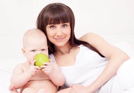 beautiful  young woman  holding her baby eating an apple at home Stock Photo - 13331130