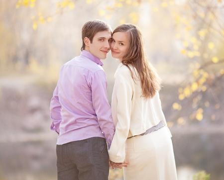 jovenes enamorados: retrato de un bajo contraste de una feliz pareja de jóvenes al aire libre en el parque de otoño