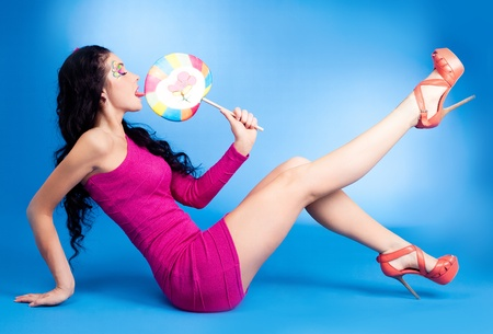 sexy tongue: pretty young brunette woman with a lollipop, isolated against blue background