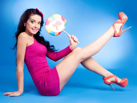 pretty young brunette woman with a lollipop, isolated against blue background photo