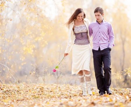 肖像画の幸せな愛情のあるカップル歩行屋外秋の公園で