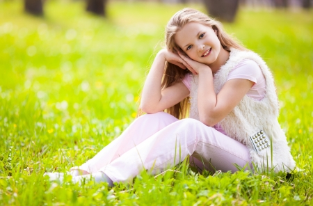 outsides: pretty teenage girl sitting on the grass in the summer park