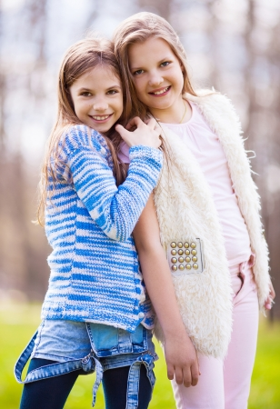 outsides: two girls embracing and laughing  in the summer park