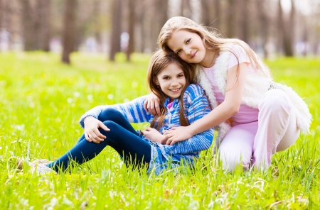 two girls embracing and laughing  in the summer park photo