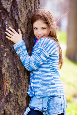 nine years old: happy nine year old  girl standing near the tree in the summer park