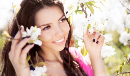 outsides: beautiful young brunette woman standing near the apple tree on a warm summer day