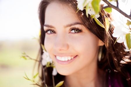 gyönyörű, fiatal, barna nő áll közel az almafa egy meleg nyári napon