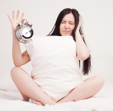 unhappy woman waking up in the morning and switching off the alarm clock   photo
