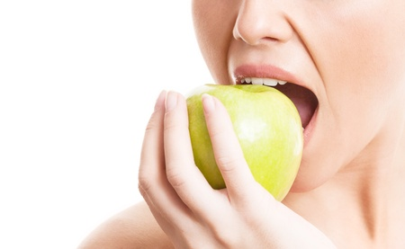 closeup of the face of a woman eating a green apple, isolated against white background, copy space for your text to the left photo