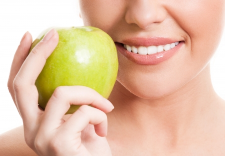 food hygiene: closeup of the face of a woman holding a green apple, isolated against white background