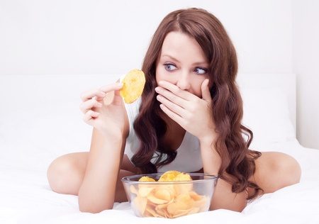 pretty woman eating potato chips in bed at home  and scared of gaining weight Stock Photo