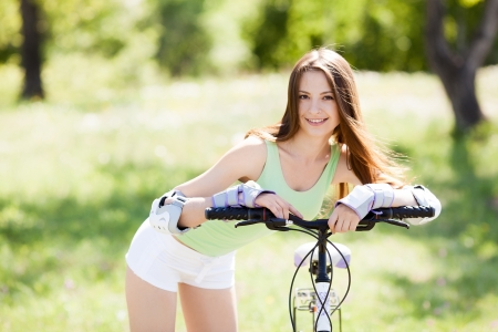 beautiful young woman  riding a bicycle on a warm summer day photo