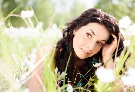 donna pensiero: riflessivo giovane donna all'aperto sul prato con fiori bianchi su un giorno d'estate