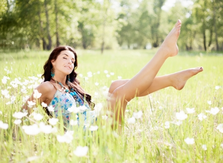 happy young  woman enjoying the sun outdoor on the grass on a summer day photo