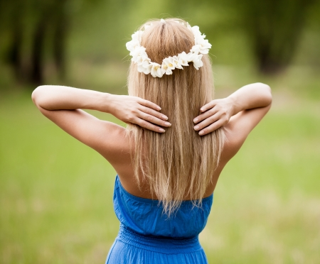 young blond woman wearing a crown of flowers outdoor on a summer day photo