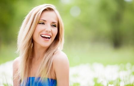 boldog, fiatal szőke nő kültéri egy nyári napon
