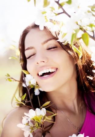 暖かい夏の日の公園の美しい若いブルネットの女性