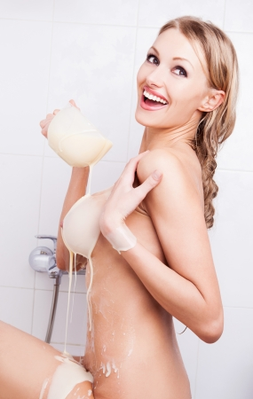 body milk: sexy young nude blond woman pouring condensed milk on her body
