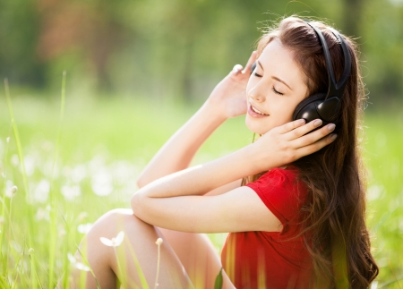 summer wear: happy young brunette woman listening to the music outdoor on a summer day