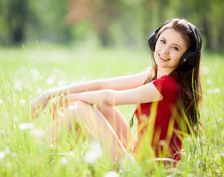 happy young brunette woman listening to the music outdoor on a summer day photo