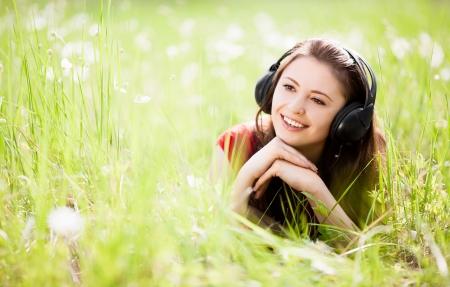夏の日に屋外の音楽を聴く幸せな若いブルネットの女性