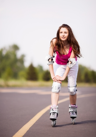 roller blade: happy young brunette woman roller skating in the park