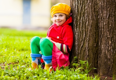 outsides: happy five year old girl sitting near the tree on a summer day
