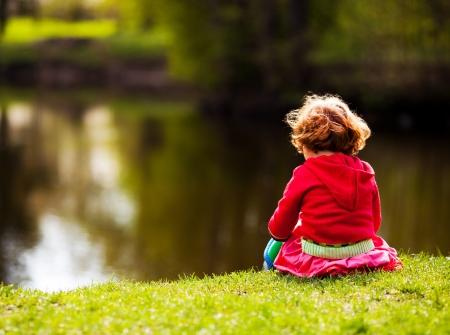 niña de cinco años de edad sentado en la orilla del río en un día de verano