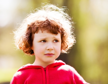 five years old: upset five year old girl in the summer park Stock Photo