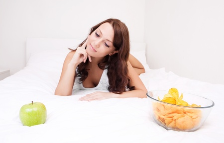 happy young woman choosing between an apple and potato chips in bed at home   photo