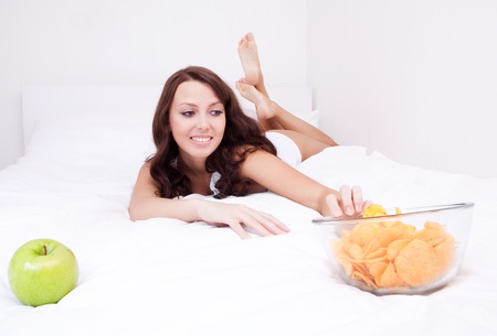 bad apple: happy young woman choosing between an apple and potato chips in bed at home