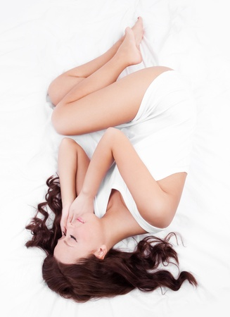 slim young brunette woman sleeping peacefully on the white linen in bed at home, top view