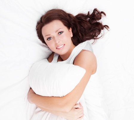 young brunette woman  with a pillow in bed at home, top view Stock Photo - 14182246