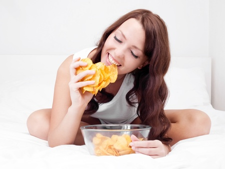gain: pretty woman eating potato chips in bed at home   Stock Photo