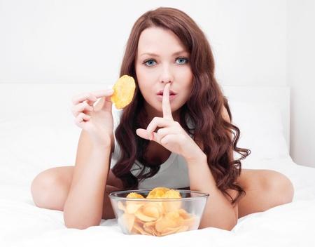 guardar silencio: mujer bonita comer papas fritas en la cama en su casa con el dedo en los labios