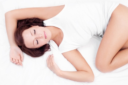peacefully: slim young brunette woman sleeping peacefully on the white linen in bed at home, top view