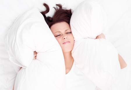displeased  young brunette woman frowning and closing her ears with pillows, in bed at home Stock Photo - 14182410