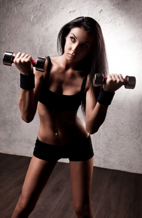 petite: hight contrast portrait of a  beautiful young woman working out with dumbbells in the gym