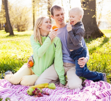 happy young family having a picnic in the park on a summer day   focus on the woman  photo