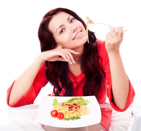 mooie jonge brunette vrouw het eten van spaghetti met groenten en ketchup in huis Stockfoto