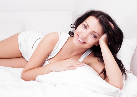 beautiful thoughtful young brunette woman relaxing in bed at home photo