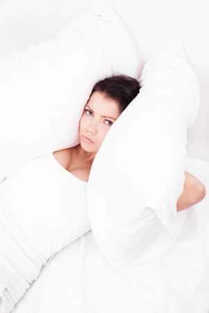 displeased  young brunette woman frowning and closing her ears with pillows, in bed at home, top view Stock Photo - 14198011
