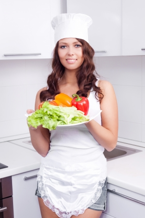 sexy housewife: beautiful young woman with vegetables in the kitchen at home