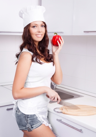 beautiful young brunette woman cooking in the kitchen at home photo