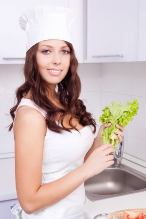 sexy housewife: beautiful young woman with salad in the kitchen at home
